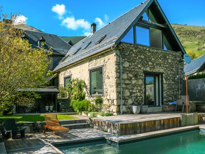 Stunning  5 bedroom stone house with panoramic views and heated swimming pool. An exceptional location in a calm mountain village between 2 popular ski resorts. Prosperous Gite business completely renovated for contemporary deluxe living.